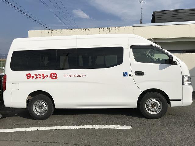 白い車体に赤いロゴの送迎車です